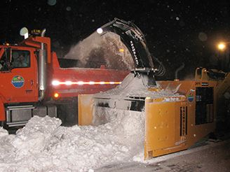 equipment blowing snow into a dump truck for removal